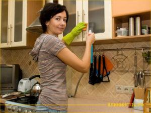 Девушка с моющим средством и губкой протирает кухонный гарнитур
